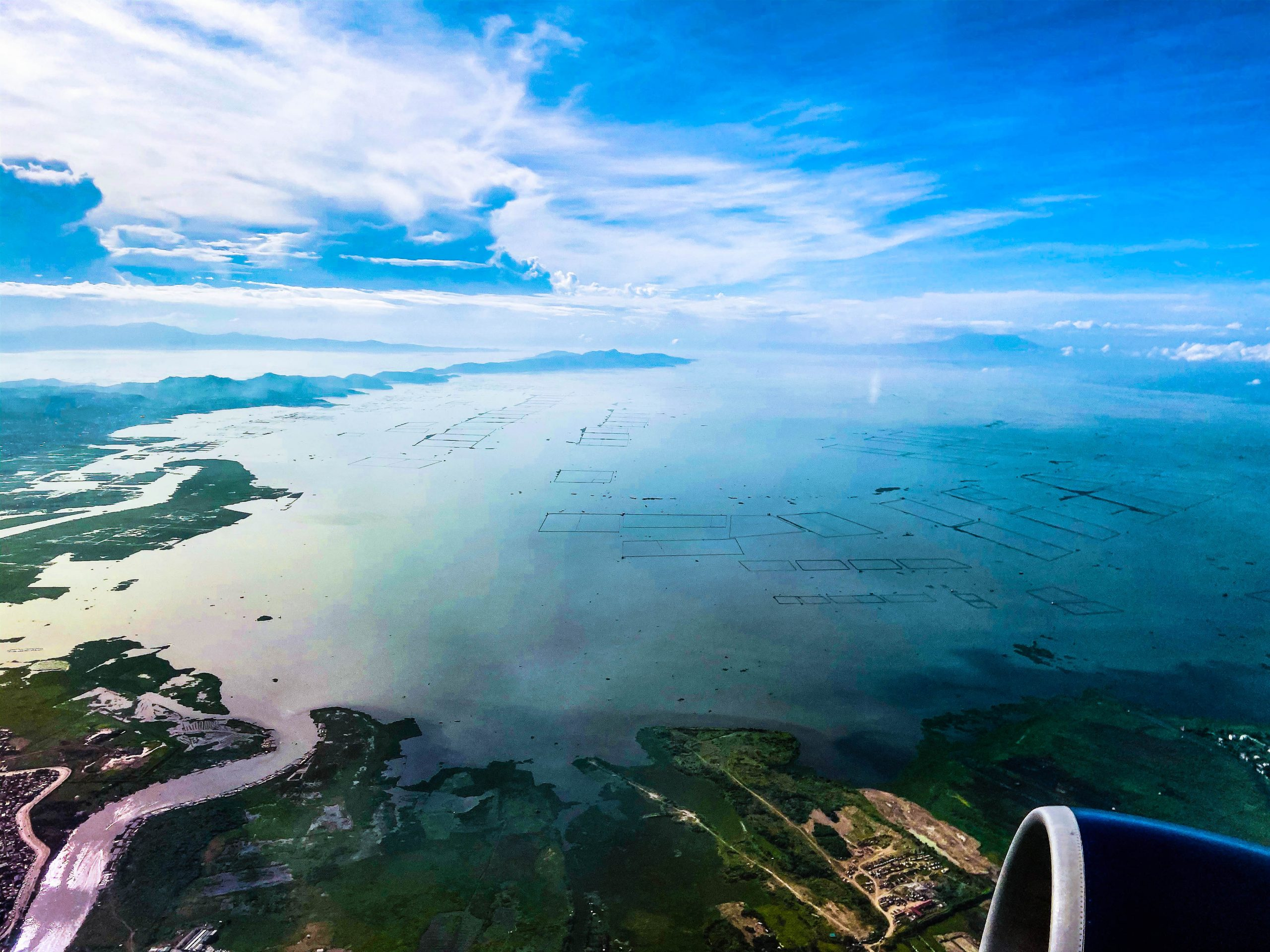 An aerial view of a wide body of water (Laguna de Bay, to be specific, the largest of all lakes in the Philippines)
