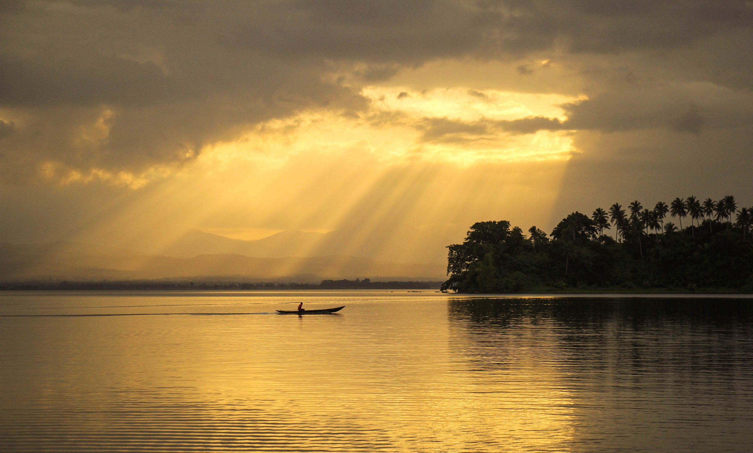 In the distance, a lone boat floats through a vast lake (Naujan Lake, to be specific, one of the largest lakes in the Philippines) illuminated by shafts of sunlight streaming through the clouds