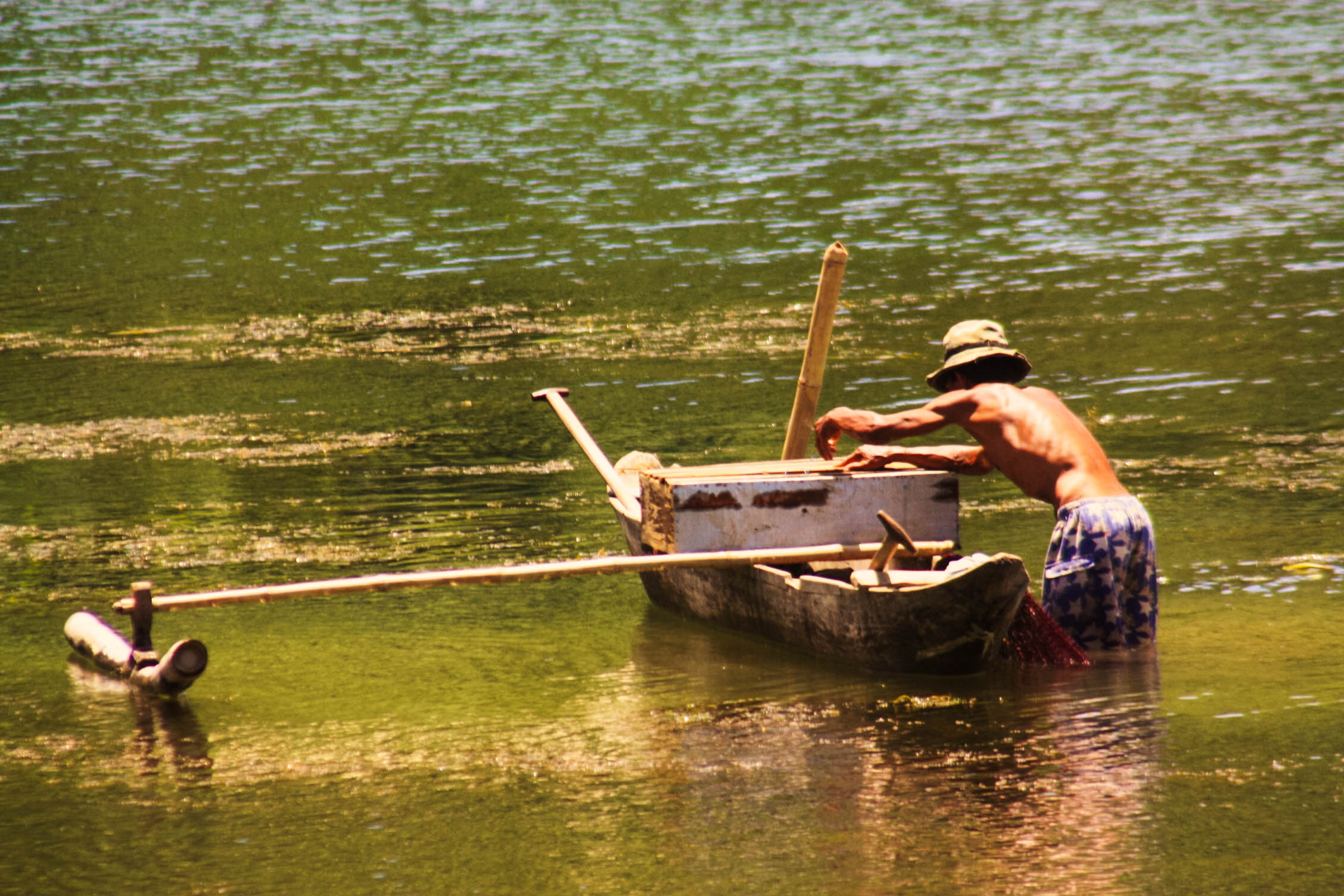 A man standing in murky waters, hauling in an outrigger boat