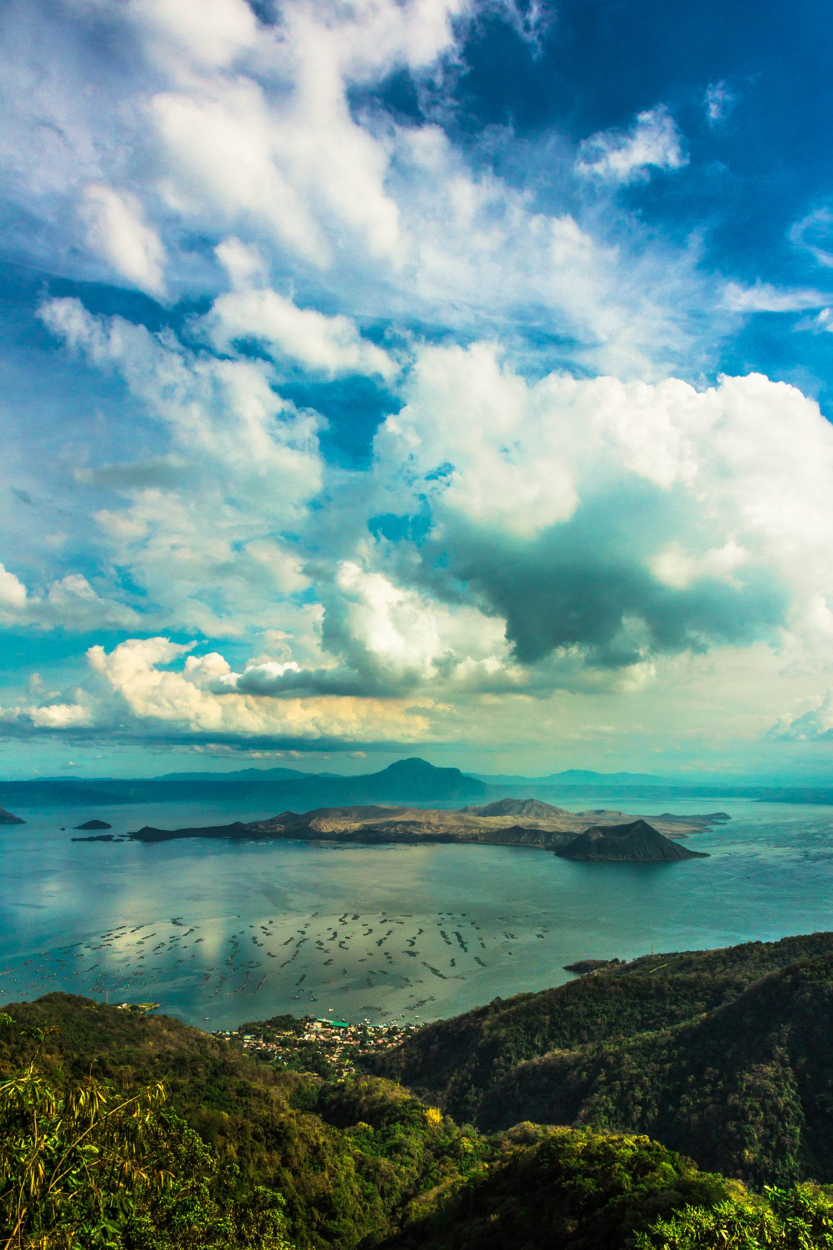 A view of a vast body of water (Taal Lake, to be exact, one of the largest lakes in the Philippines) with islands in its midst beneath a partially cloudy sky