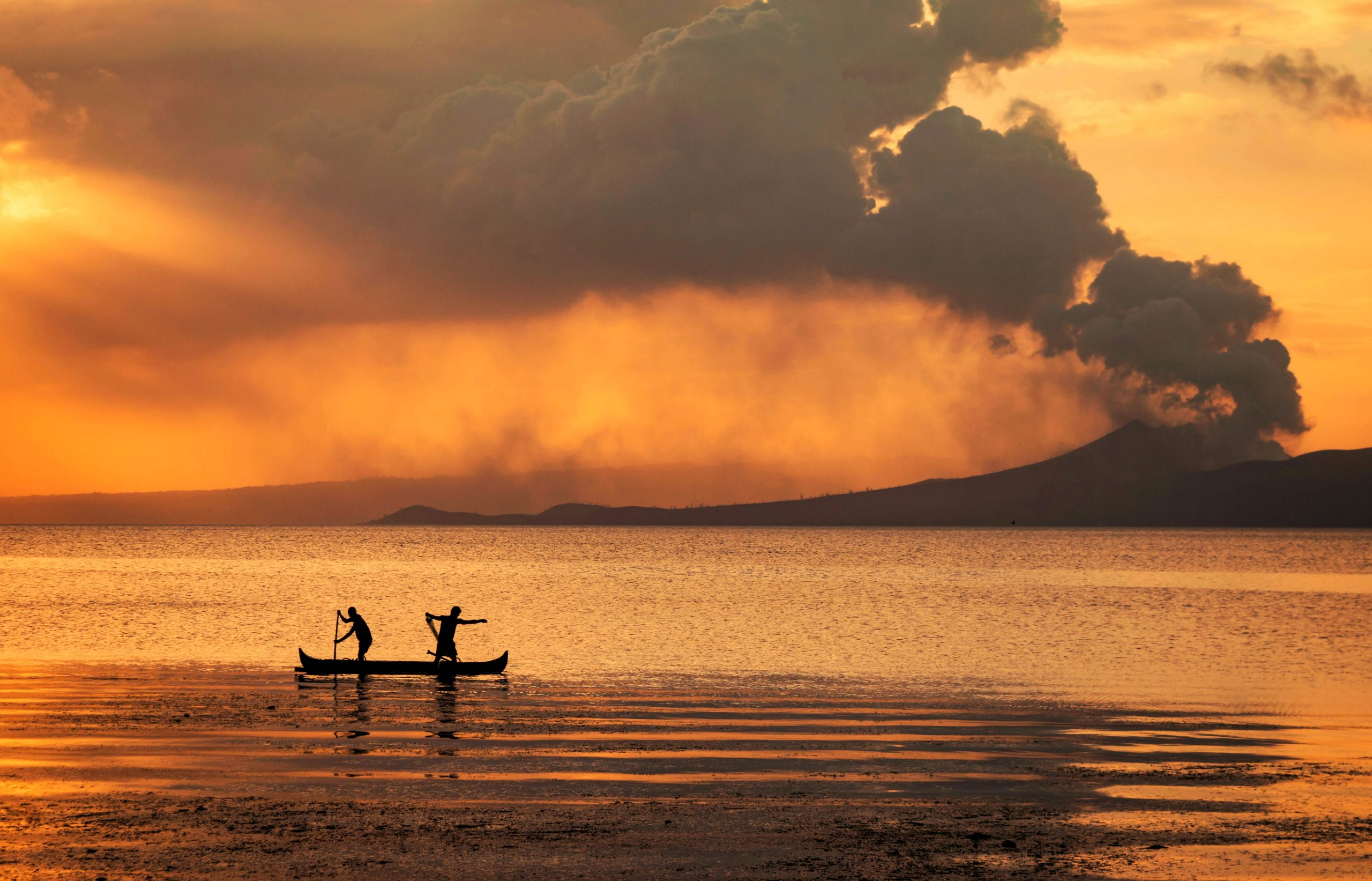 Two men on a boat sailing across a vast body of water while behind them a volcano erupts