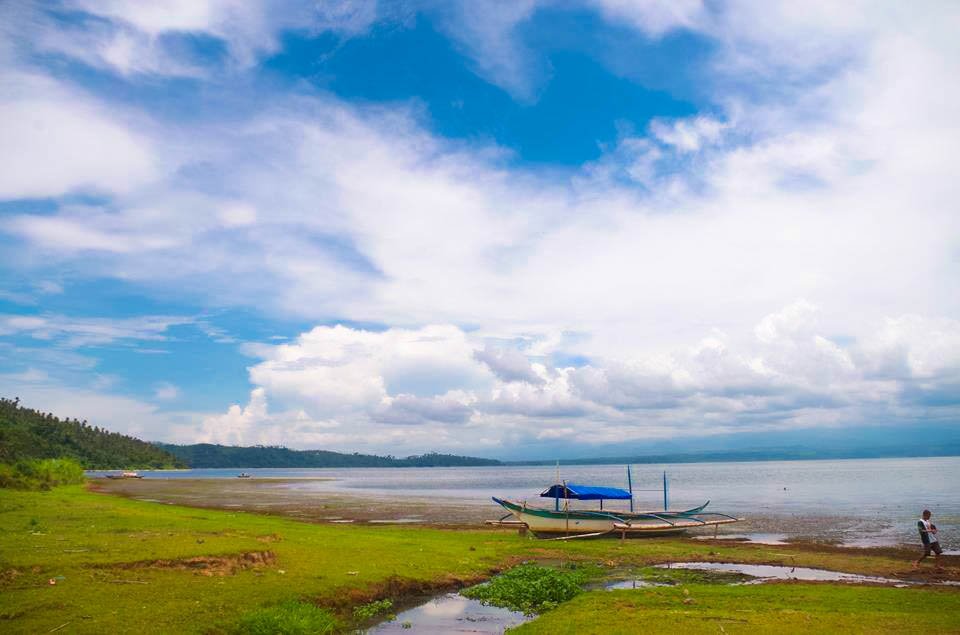 A boat moored upon a grassy shoreline, facing a wide body of water (Naujan Lake, to be exact, one of the largest lakes in the Philippines) beneath a blue sky largely covered by white clouds