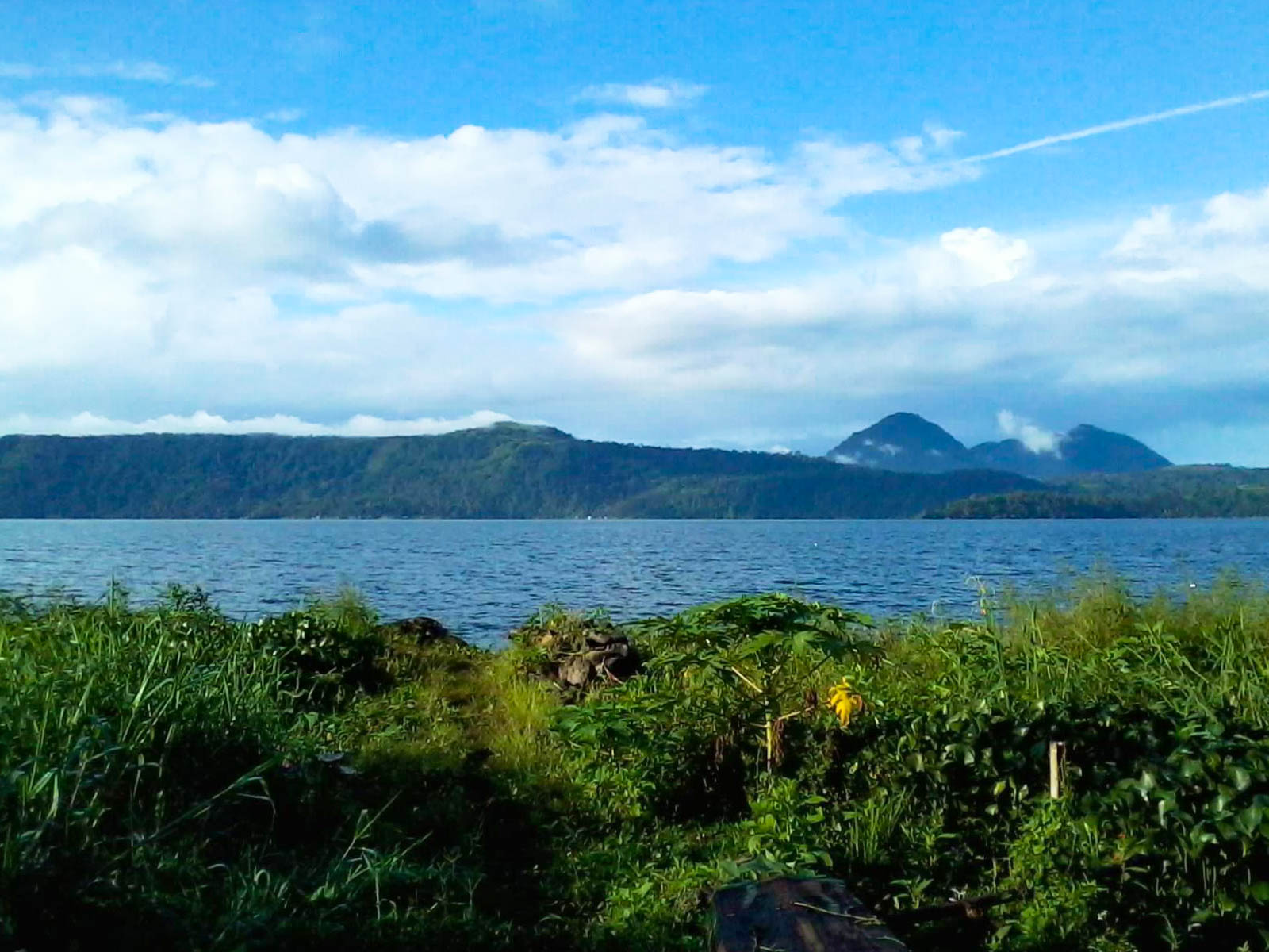 Vegetated land overlooking a vast body of water (Lake Lanao, one of the largest lakes in the Philippines) backdropped by mountains beneath a partially cloudy sky
