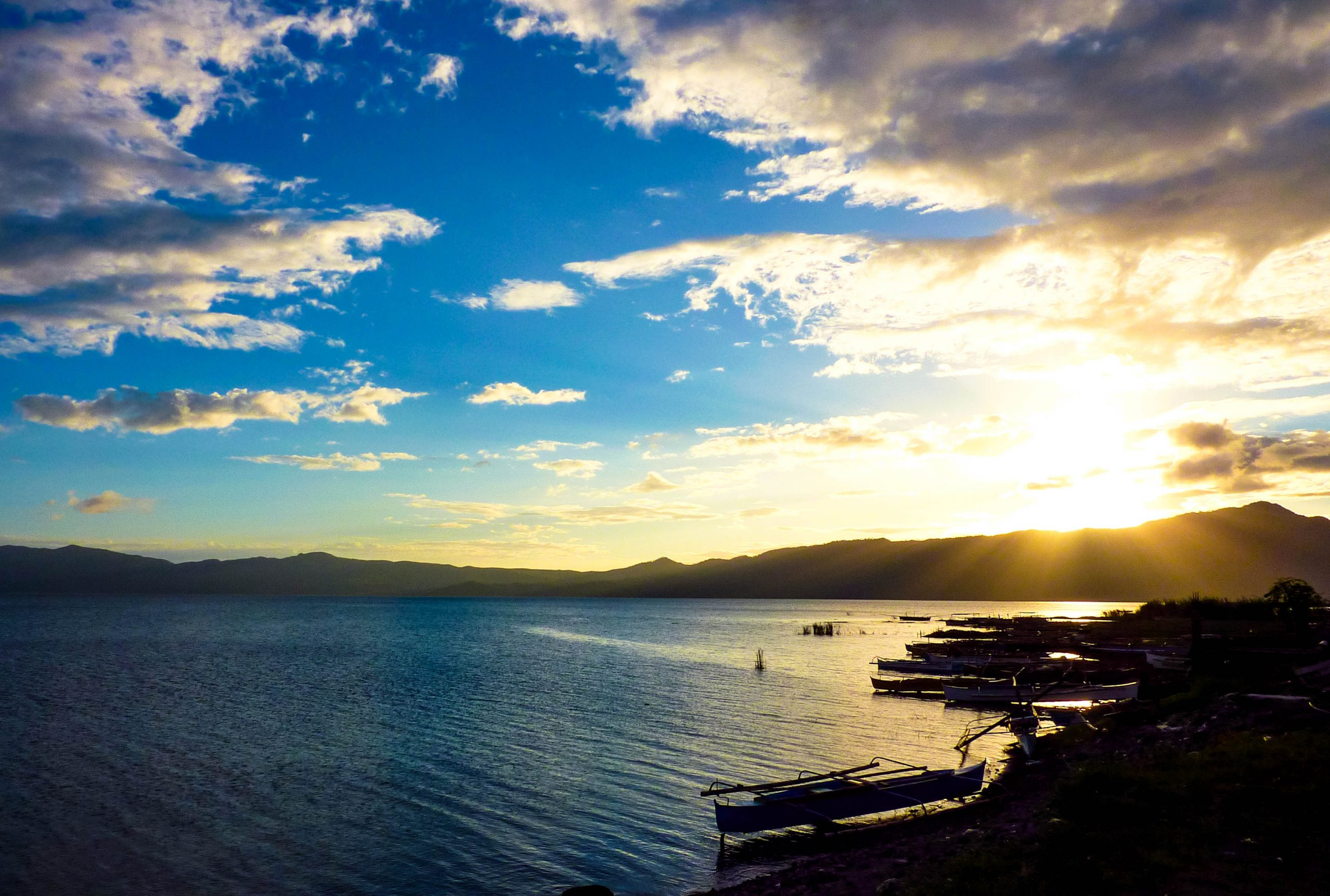 Sunrise illuminates a vast body of water (Lake Mainit, to be specific, one of the largest lakes in the Philippines) beneath a blue sky partially covered with clouds