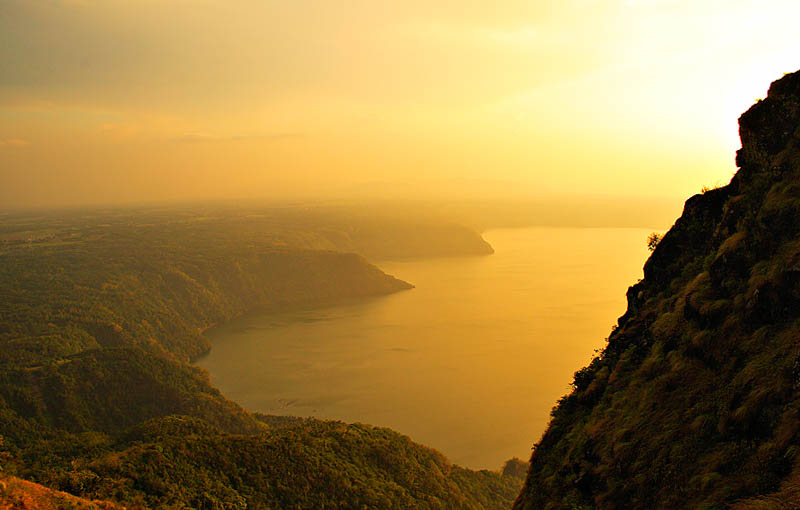 A vas body of water (Taal Lake, to be exact, one of the largest lakes in the Philippines) surrounded by cliffs illuminated in a hazy light