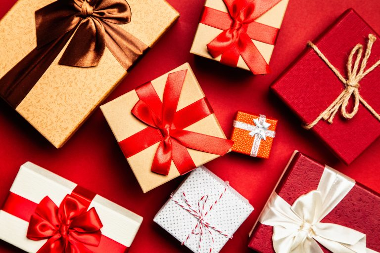 A top view shot of christmas gifts, used as a featured image for the article Perfect Travel Gifts for Christmas 2020 (that People Can Actually Use While Traveling), a guide for the perfect travel gift for Christmas 2020, on phmillennia.com
