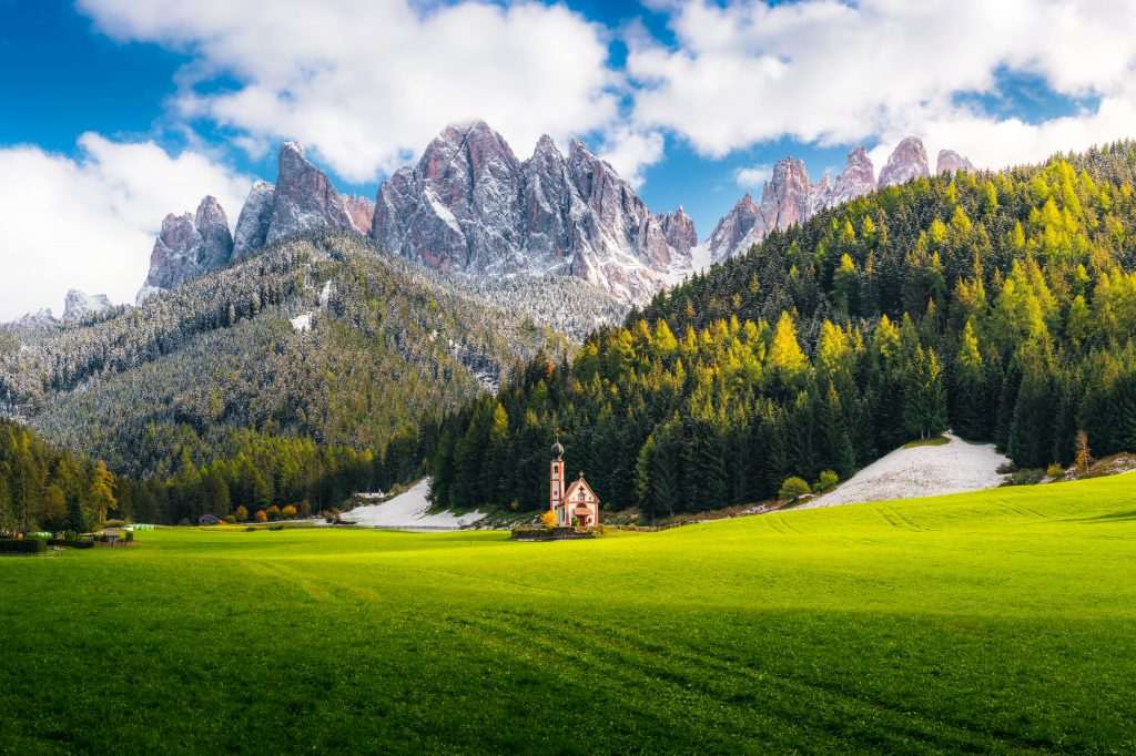 "A little church stands in a green field backdropped by forest-clad slopes and jagged peaks beneath a cloudy sky, a featured image used in the article ""Heubad: The Alpine Tradition of Hay Bathing"" on phmillennia.com"