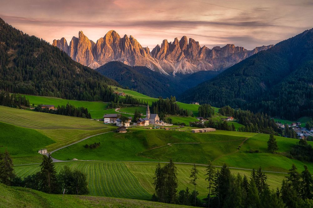 """A small village in a green field with trees, backdropped by jagged peaks, an image used in the article """"Heubad: The Alpine Tradition of Hay Bathing"""" on phmillennia.com"""