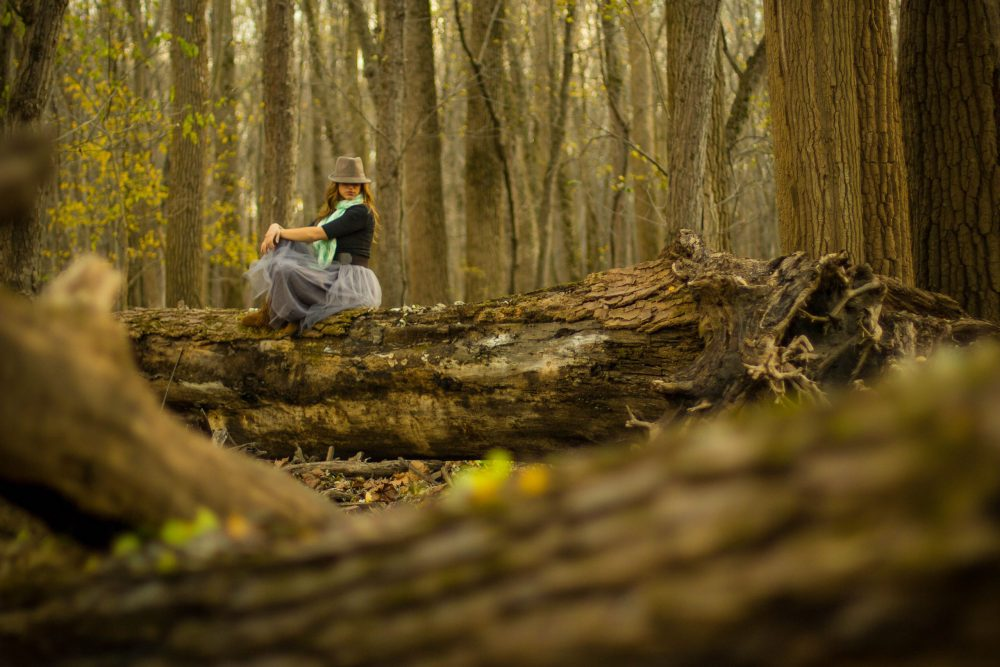 A woman in a dress sitting atop a log in the middle of a forest