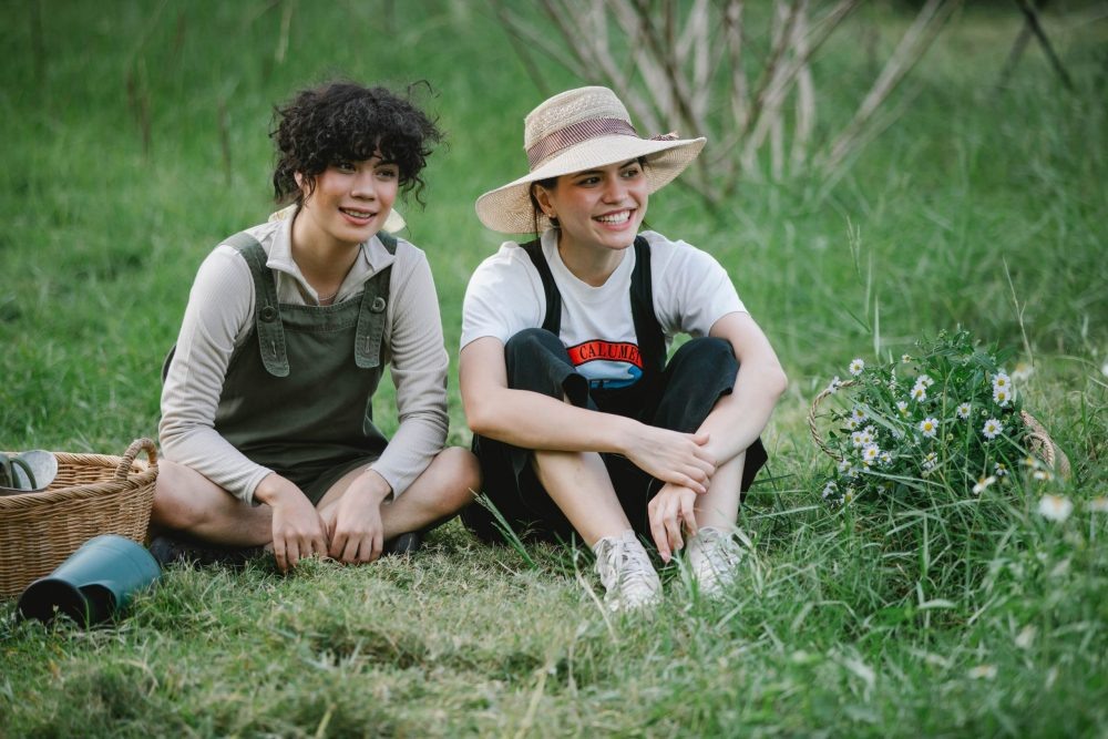 Two women in overalls sitting on a grassy field