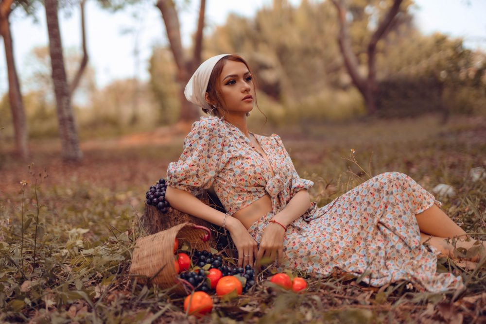 A woman in traditional dress reclining upon a grassy field surrounded by a basket with spilled fruits