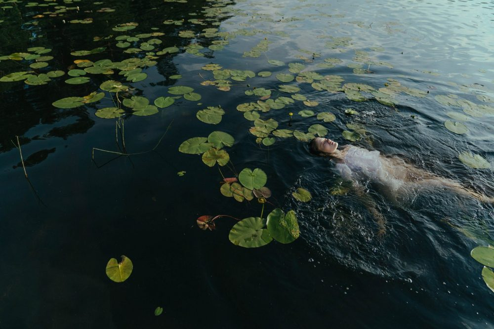 A woman in white dress floating upon a body of water covered with lily pads, perhaps a depiction of cottagecore