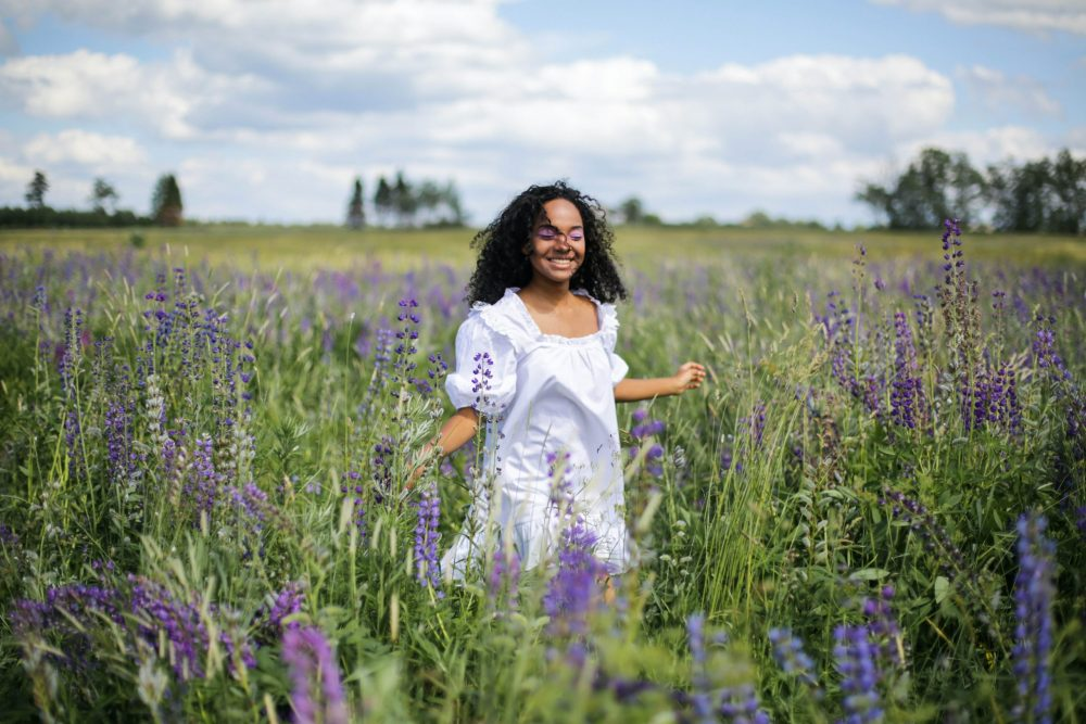 A young black woman in white dress running through a field of violet flowers, perhaps a depiction of cottagecore