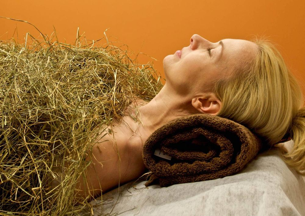 An image of a woman covered with hay, with her head upon a roll of cloth, clearly engaging in heubad