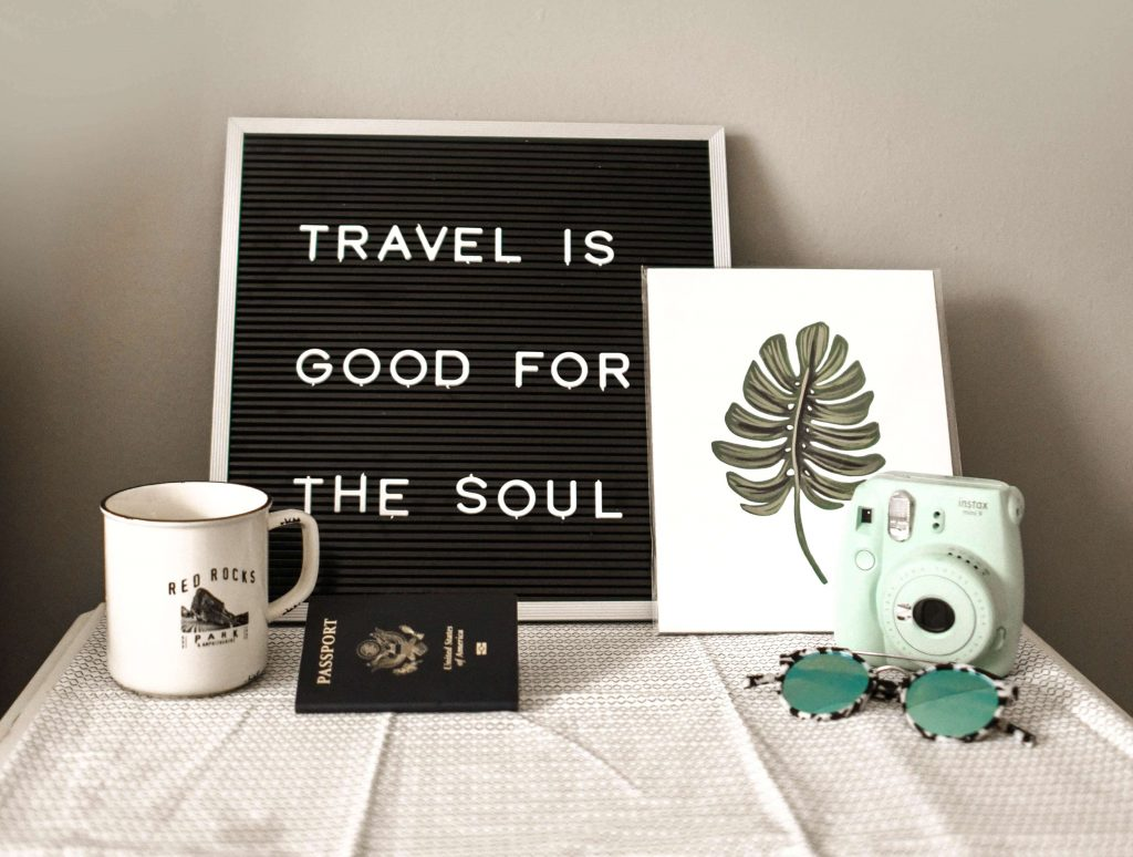 An image of a mug, travel-themed decor, and other small items on a table, used as a featured image for the article 'The Best Travel-Inspired Home Décor Ideas and Inspiration' on phmillennia.com