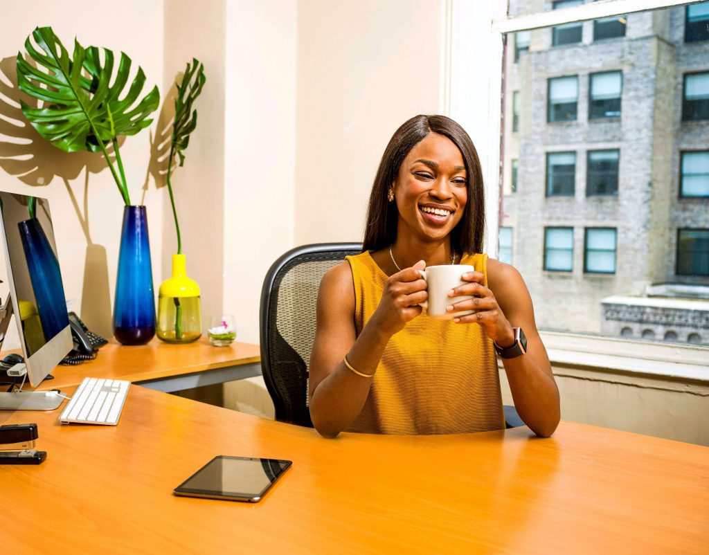 """A boss lady smiling while sitting on a home office chair on her home office work desk, used as the featured image for the article """"Best Home Office Chairs for Boss Ladies"""" on phmillennia.com"""