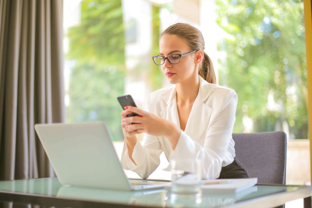 """A woman in business clothing, staring at her phone, while seated in front of a desk with a laptop on it, used as the featured image for the article """"Google Opinion Rewards: Get Paid for Your Opinion"""" on phmillennia.com"""