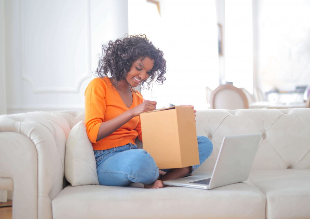 """A woman on a couch inspecting a box beside a laptop, used as the featured image for the article """"Amazon Prime Day 2021: Get Exclusive Deals and More!"""" on phmillennia.com"""