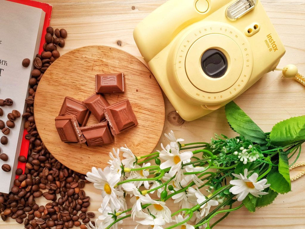 """An image of a camera, flowers, chocolates, and other assorted things on top of a brown surface, used as the featured image for the article """"It's 2021. Is It Too Late to Start a Blog? (Hint: It's Not, But You Should Find Out Why)"""" on phmillennia.com"""