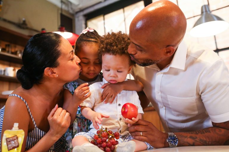 """An image of a black family, including a black father, a black mother, and two black children, all hugging and kissing together, used as the featured image for the article """"Cool and Useful Gift Ideas for Father's Day"""" on phmillennia.com"""