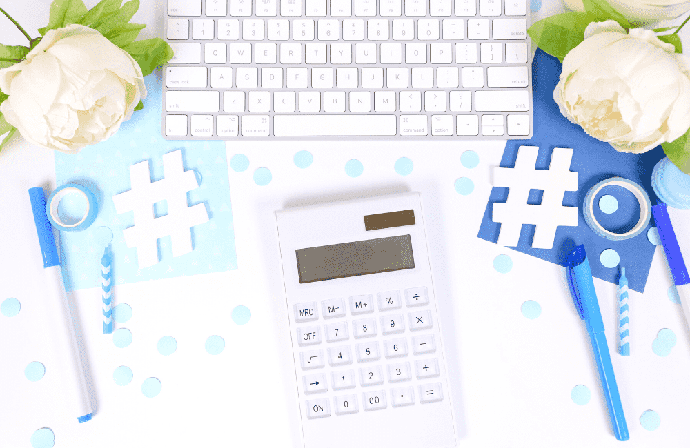 """An image of a calculator, keyboard, roses, and other things spread on a white surface, used as an image for the article """"It's 2021. Is It Too Late to Start a Blog? (Hint: It's Not, But You Should Find Out Why)"""" on phmillennia.com"""