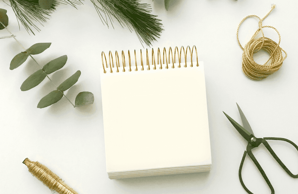 """An image of a notebook beside a pair of scissors, yarn, pen, and leaves,, used as an image for the article """"It's 2021. Is It Too Late to Start a Blog? (Hint: It's Not, But You Should Find Out Why)"""" on phmillennia.com"""