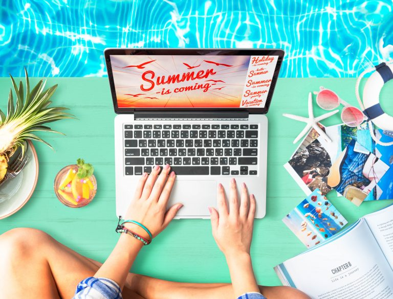 """A mockup of a laptop and other beach- and summer-themed items and accessories, used as a featured image for the article """"500 Summer Blog Post Ideas for Every Niche"""" on phmillennia.com"""