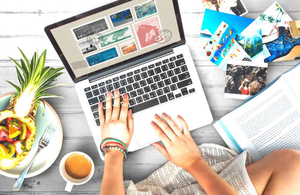 """An aerial view of a pair of hands on a laptop surrounded by various objects related to summer, used in the article """"Summer Bloggin': 10 Awesome Reasons to Start a Blog This Summer"""" on phmillennia.com"""
