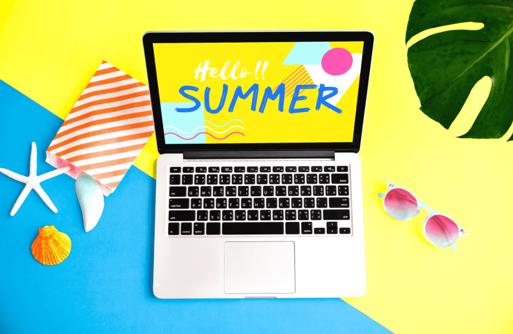 """An image of a laptop surrounded by various objects related to summer, used in the article """"Summer Bloggin': 10 Awesome Reasons to Start a Blog This Summer"""" on phmillennia.com"""