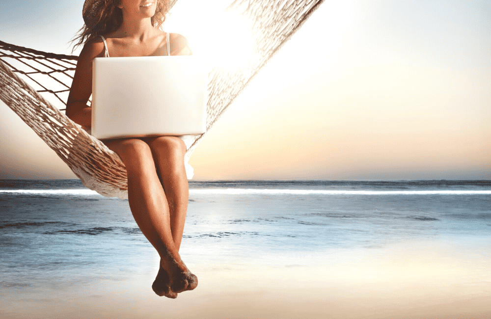 """A woman using a laptop while sitting on a hammock on the beach, used in the article """"Summer Bloggin': 10 Awesome Reasons to Start a Blog This Summer on phmillennia.com"""""""