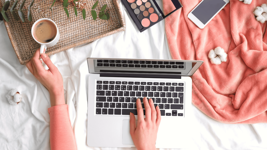 """A flatlay image of a laptop being used, surrounded by various objects, used as the featured image for the article """"Comfy Work from Home WFH Clothes for Women"""""""