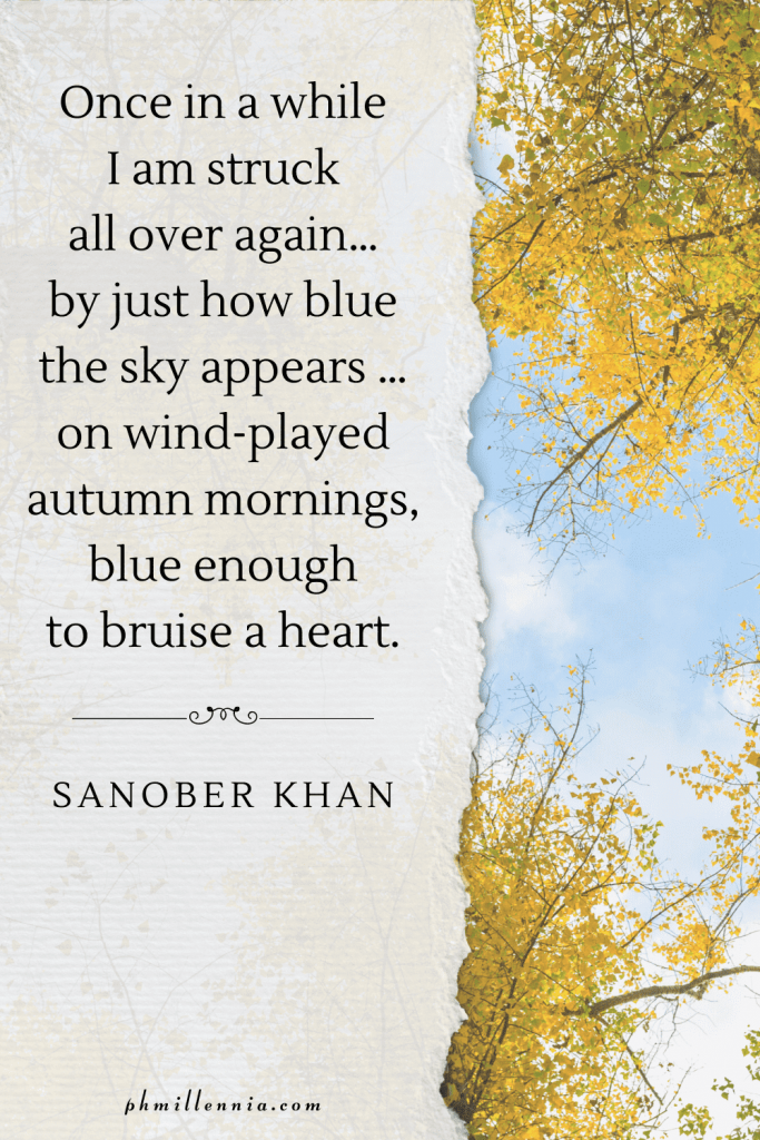 A graphic featuring an autumn quote/fall saying over an image of a trees in autumn/fall season backdropped by a blue sky