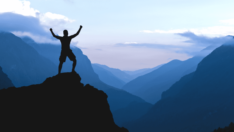 """An image of a silhouette of a man standing on a high rock overlooking a mountainous landscape, used as the featured image for the article """"199 Quotes on Success to Inspire You to Greatness"""" on phmillennia.com"""