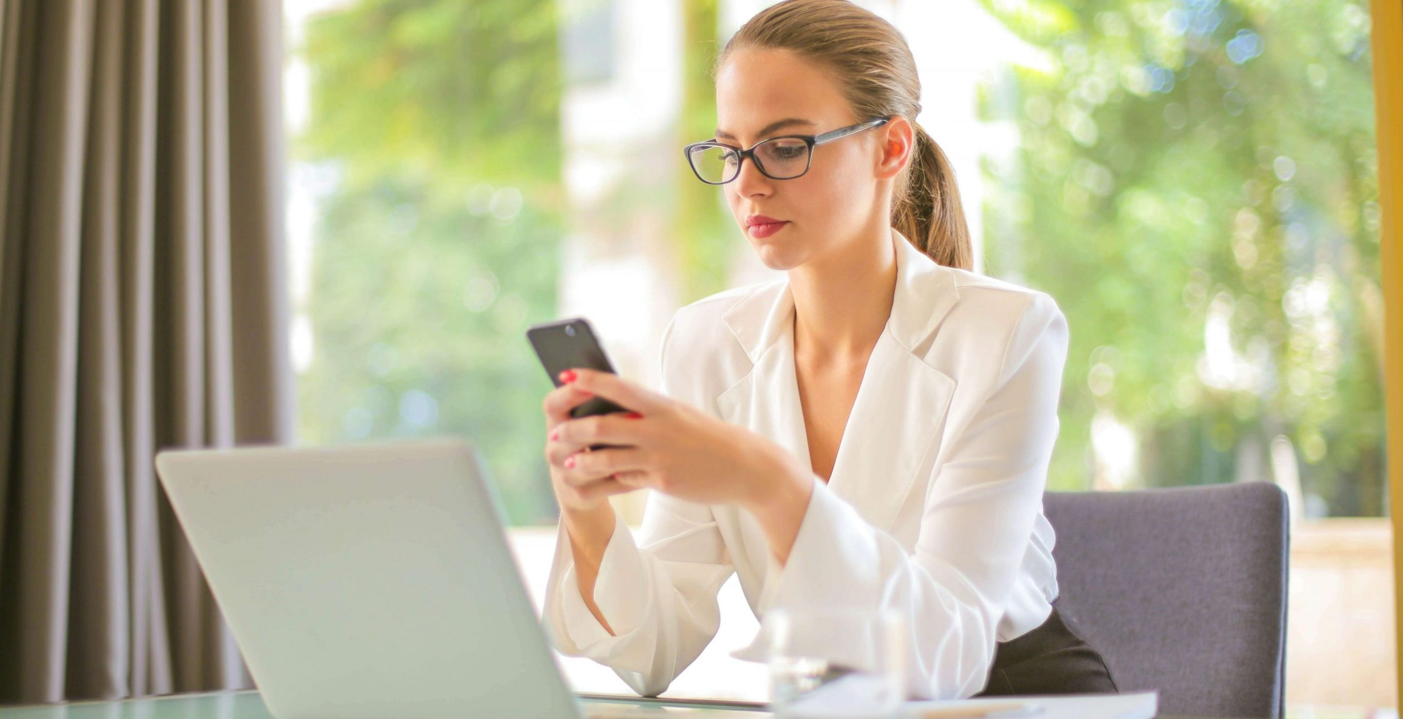 A woman in business clothing, staring at her phone, while seated in front of a desk with a laptop on it, used as the featured image for the article