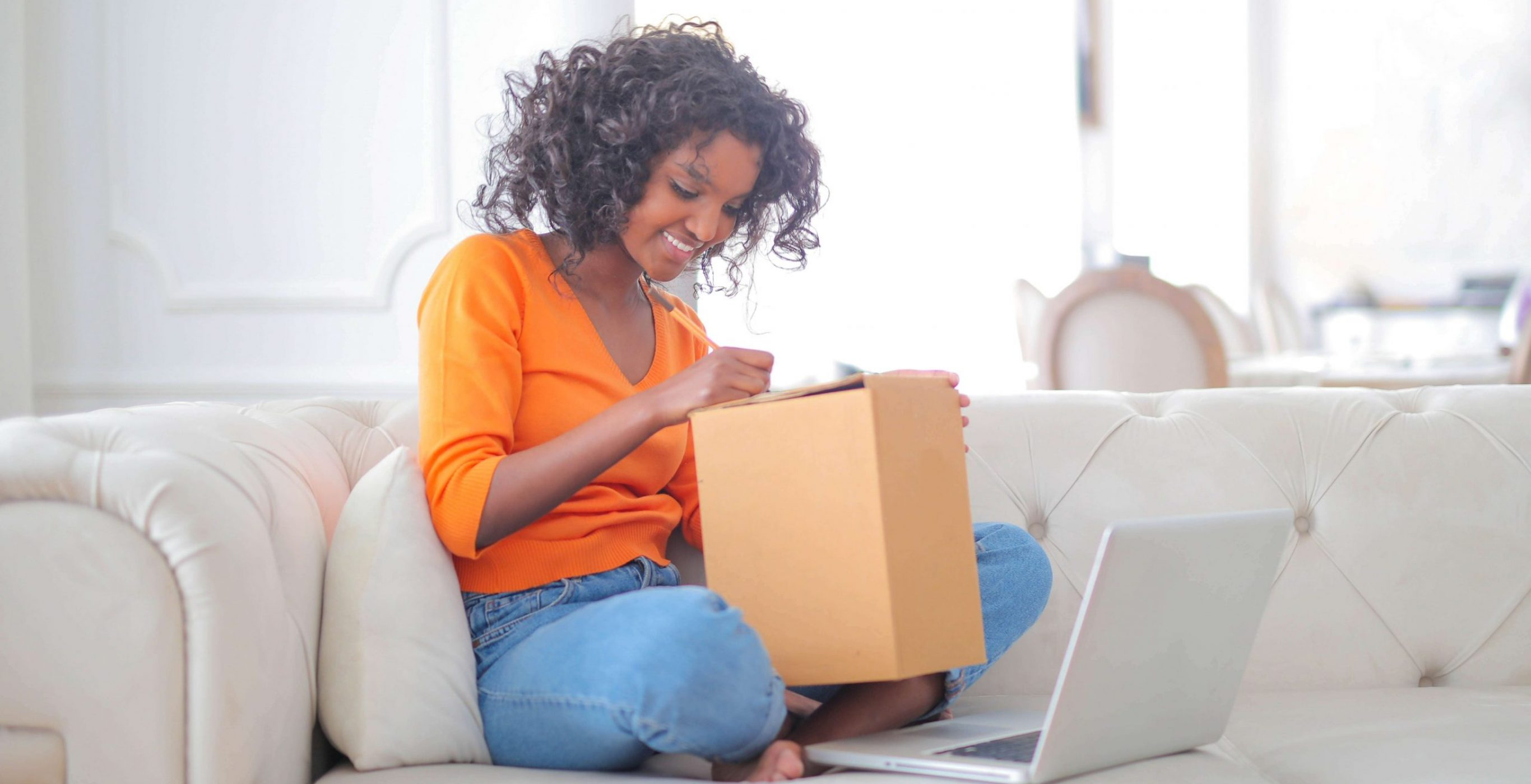 A woman on a couch inspecting a box beside a laptop, used as the featured image for the article