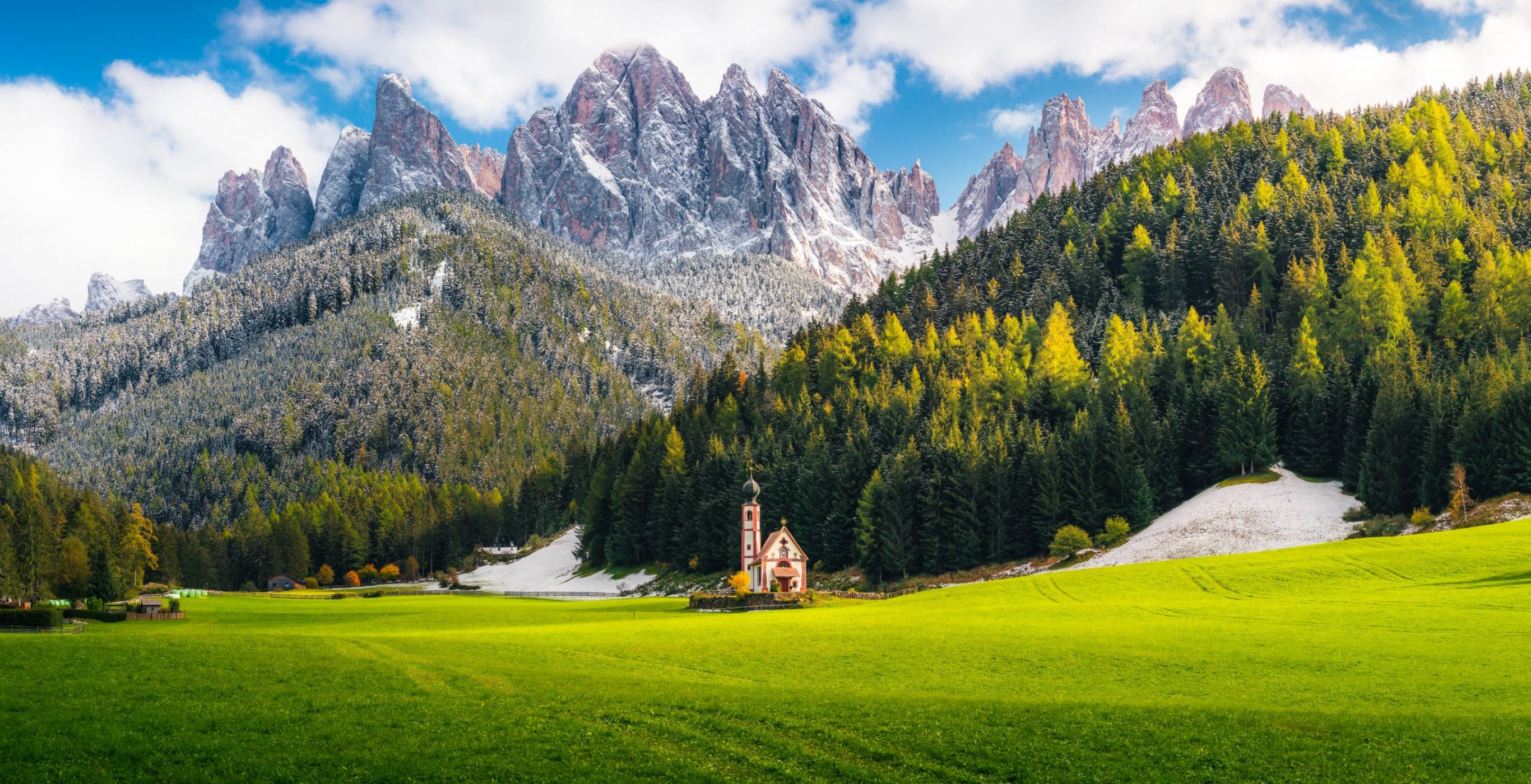 A little church stands in a green field backdropped by forest-clad slopes and jagged peaks beneath a cloudy sky, a featured image used in the article