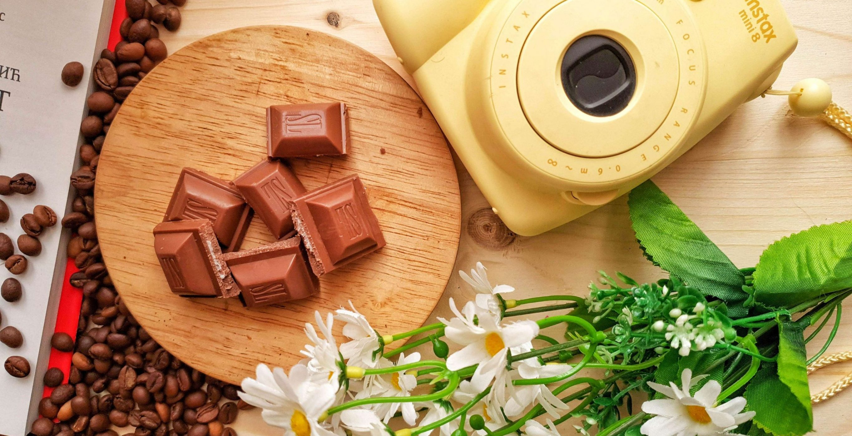 An image of a camera, flowers, chocolates, and other assorted things on top of a brown surface, used as the featured image for the article