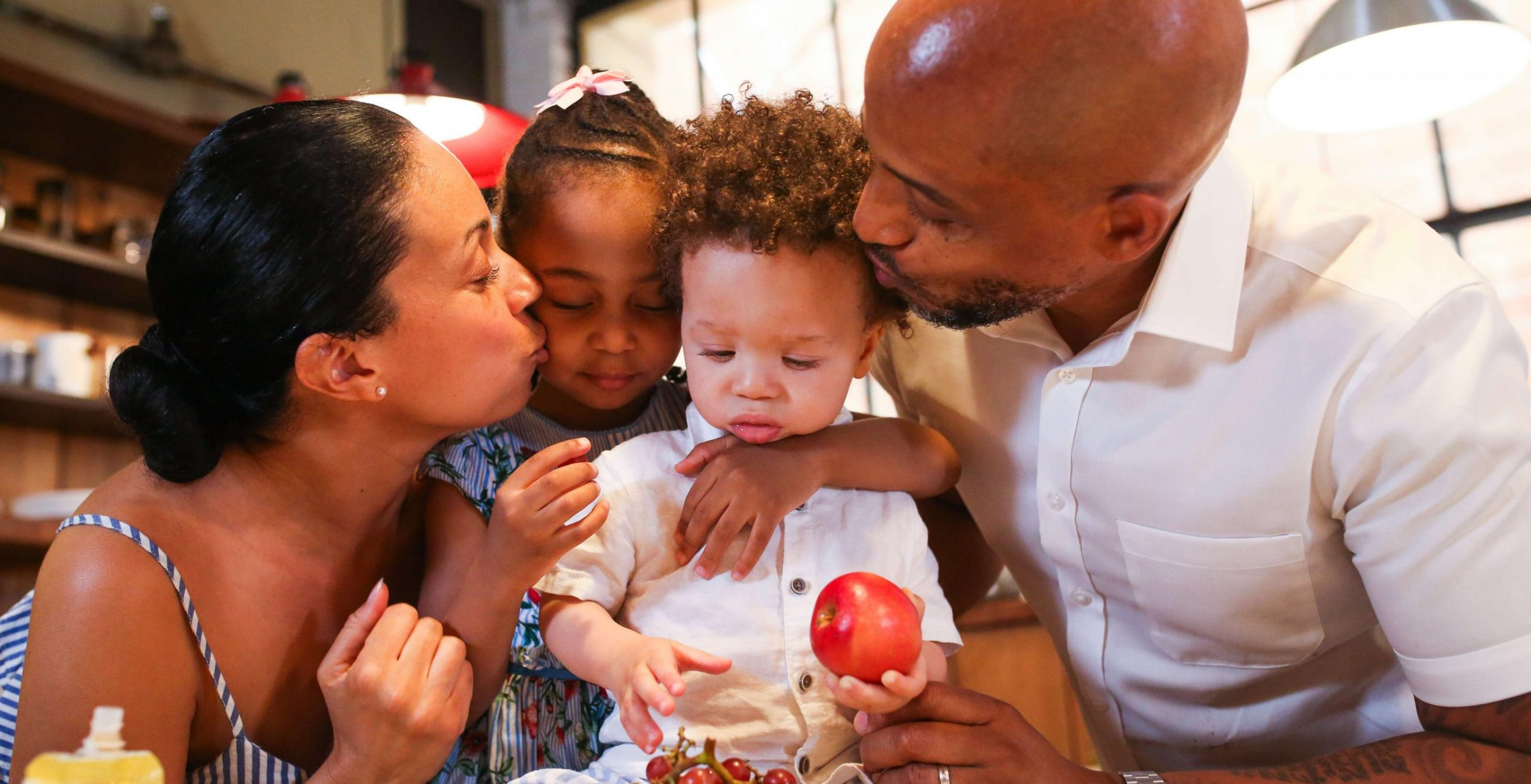 An image of a black family, including a black father, a black mother, and two black children, all hugging and kissing together, used as the featured image for the article