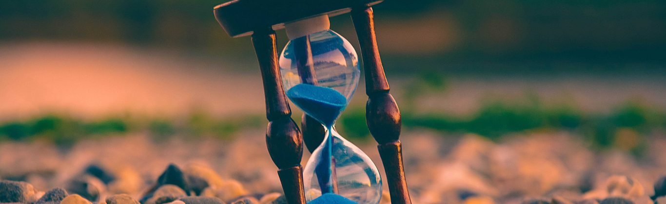 An hourglass on a pebbly ground, indicating effective time management