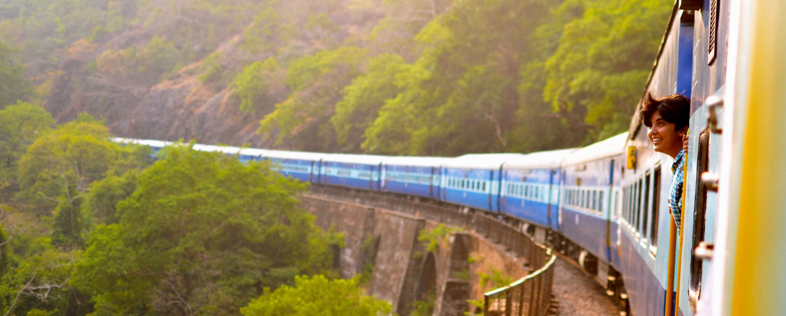 Woman staring out the window of a train passing through a verdant mountainside on a sunny day