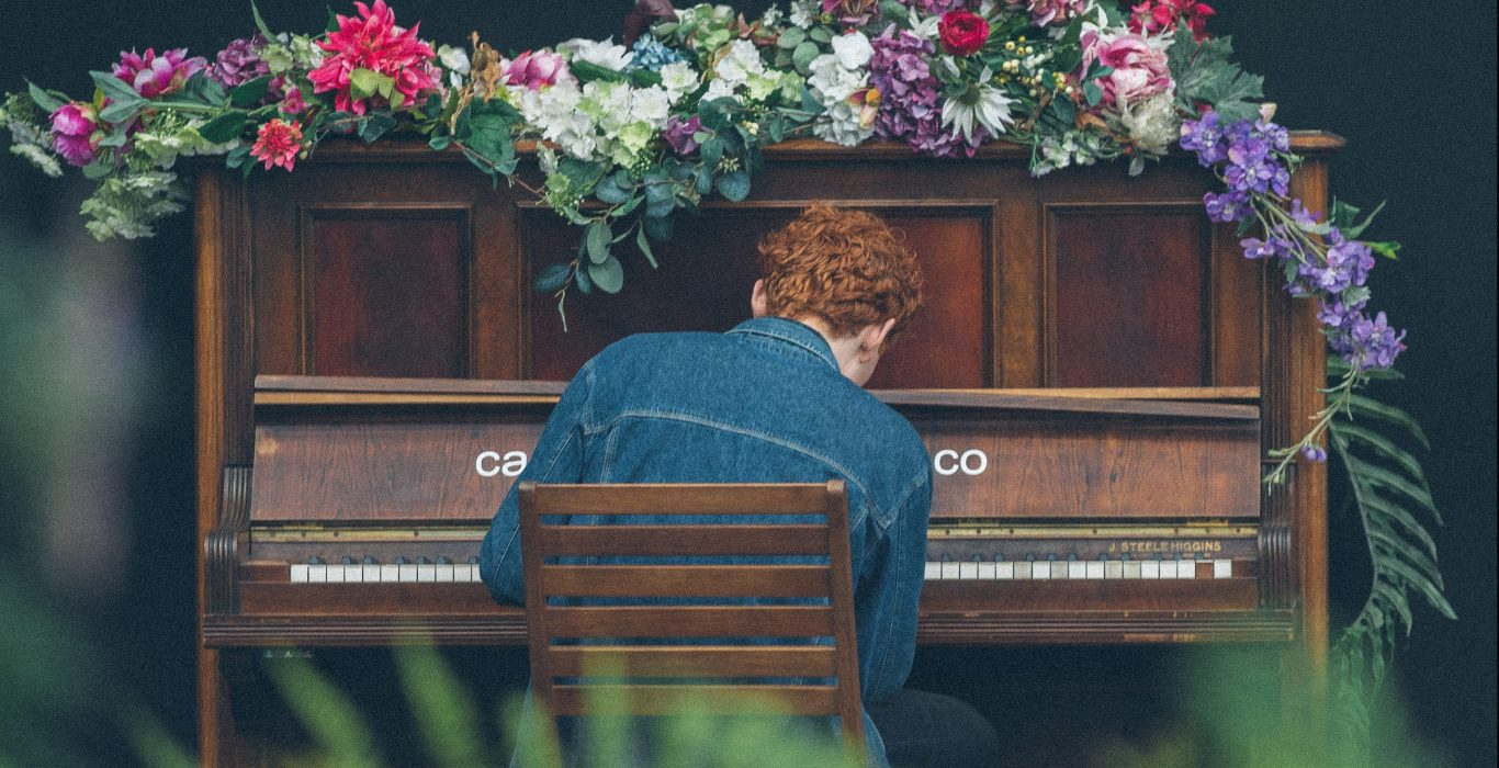 A sad man plays a piano wreathed in flowers.