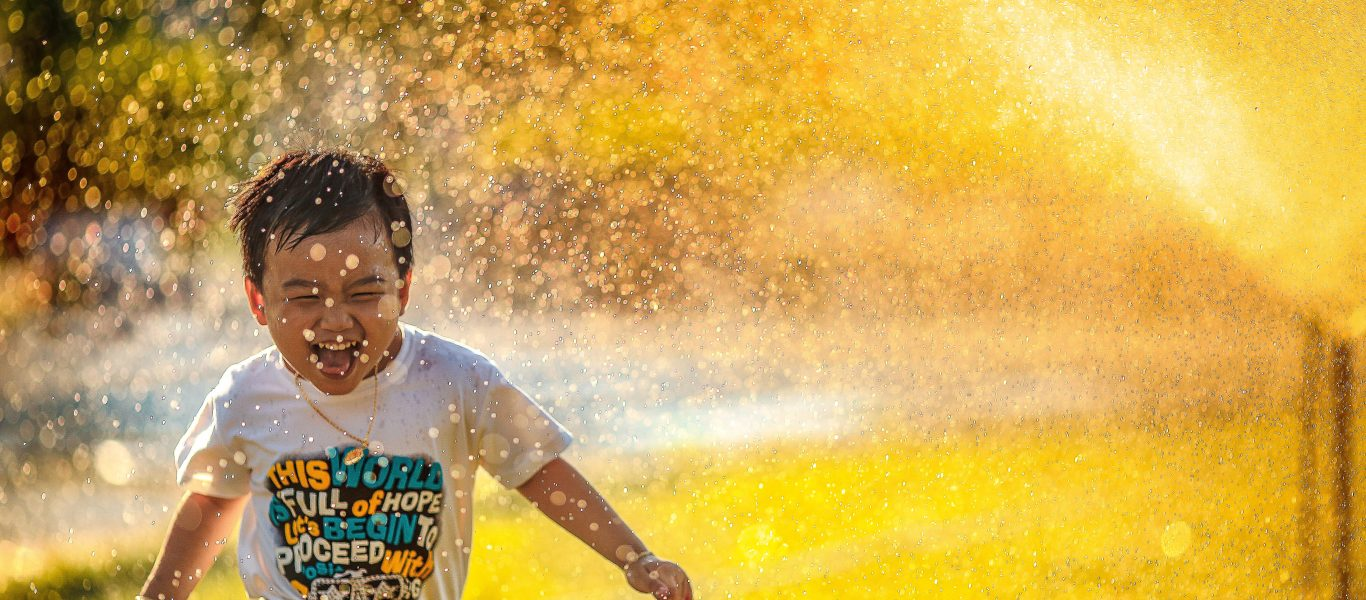 A child laughs in happiness as water from a fountain drizzles on him.
