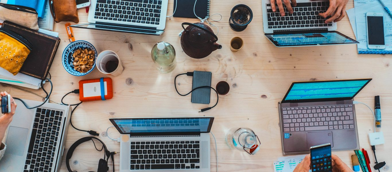 Top view of a workspace with laptops, phones, headphones, coffee mugs, etc.